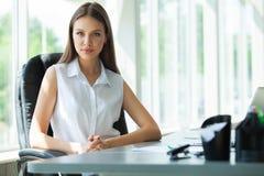 Stående av ett gladlynt affärskvinnasammanträde på tabellen i regeringsställning och se kameran royaltyfri bild