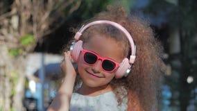 Stående av ett gulligt barn, en underbar liten härlig flicka i en vit klänning med rosa exponeringsglas och rosa hörlurar arkivfilmer