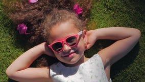 Stående av ett gulligt barn, en underbar liten härlig flicka i en vit klänning och rosa exponeringsglas som ligger på gräset lager videofilmer