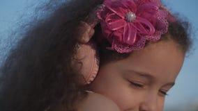 Stående av ett gulligt barn med lockigt hår, Caucasian liten flicka i en rosa klänning med en rosa blomma på hennes huvud i henne arkivfilmer