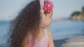 Stående av ett gulligt barn med lockigt hår, härlig Caucasian liten flickasommar i en rosa klänning med en rosa blomma på arkivfilmer