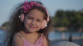 Stående av ett gulligt barn med lockigt hår, härlig Caucasian liten flickasommar i en rosa klänning med en rosa blomma på stock video