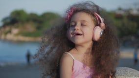 Stående av ett gulligt barn med lockigt hår, härlig Caucasian liten flickasommar i en rosa klänning med en rosa blomma på lager videofilmer