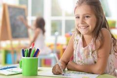 Stående av ett gulligt skolflickasammanträde på tabellen arkivfoton