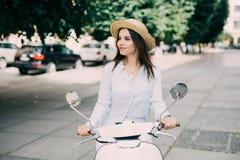 Stående av ett härligt flickadrev på den retro sparkcykeln som ler och ser kameran Fotografering för Bildbyråer