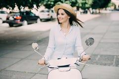 Stående av ett härligt flickadrev på den retro sparkcykeln som ler och ser kameran Arkivfoton