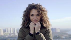 Stående av ett härligt lockigt gulligt flickaanseende på taket av en byggnad i soligt väder lager videofilmer