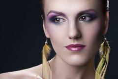 Stående av ett härligt, ung flicka med ljus färgrik makeup och fjäderörhängen på en svart bakgrund fotografering för bildbyråer