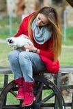 Stående av ett iklätt rött för kvinna med en katt i henne armar arkivfoto
