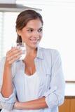 Stående av ett kvinnainnehav som ett exponeringsglas av bevattnar Arkivfoton
