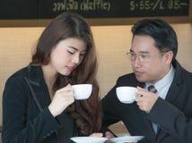Stående av ett le affärspar med kaffekoppar Arkivbilder