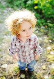 Stående av ett litet lockigt barn på en grön bakgrund Royaltyfria Foton