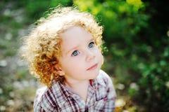 Stående av ett litet lockigt barn på en grön bakgrund Royaltyfri Foto