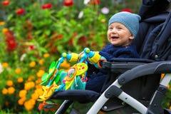 Stående av ett lyckligt barn i en barnvagn utomhus Arkivbilder