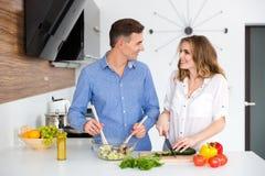 Stående av ett lyckligt härligt par som tillsammans lagar mat Royaltyfri Foto