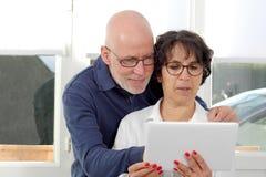 Stående av ett lyckligt högt par genom att använda den digitala minnestavlan Arkivfoto