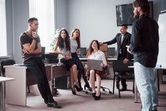 Stående av ett lyckligt idérikt lag av folk som talar i kontoret på mötet arkivfoto