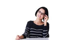 Stående av ett lyckligt kvinnasammanträde på skrivbordet Fotografering för Bildbyråer