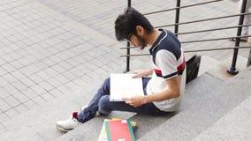Stående av ett lyckligt manligt asiatiskt studentsammanträde på trappa och läseboken lager videofilmer