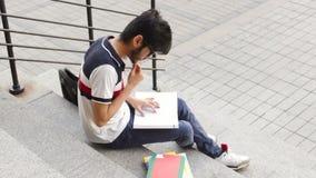 Stående av ett lyckligt manligt asiatiskt studentsammanträde på trappa och läseboken arkivfilmer