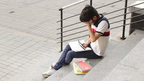 Stående av ett lyckligt manligt asiatiskt studentsammanträde på trappa och läseboken stock video