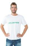 Stående av ett lyckligt manligt volontäranseende med händer på höfter arkivfoto