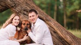 Stående av ett lyckligt par med deras husdjur royaltyfria bilder