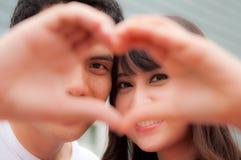Stående av ett lyckligt par som ler show deras händer som hjärta Royaltyfria Bilder