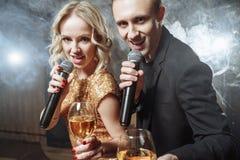 Stående av ett lyckligt ungt par med mikrofoner och exponeringsglas i en karaokestång arkivfoton