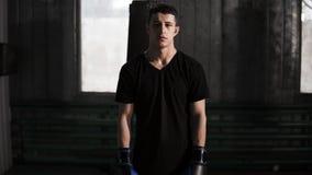 Stående av ett manligt boxareanseende för mörk haired caucasian i en gammalmodig boxas idrottshall nära sandpåsen Bära som är til lager videofilmer