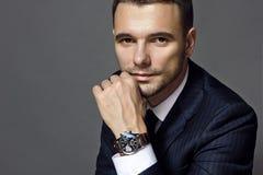 Stående av ett mansammanträde med en dräkt med en klocka, studio royaltyfri fotografi