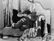 Stående av ett mansammanträde på en soffa som rymmer en fan (alla visade personer inte är längre uppehälle, och inget gods finns  arkivfoton