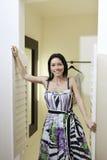 Stående av ett mitt- anseende för vuxen kvinna på dörröppningen av loge i modeboutique arkivbilder