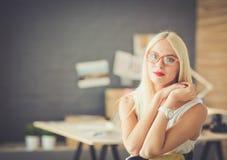 Stående av ett moget affärskvinnasammanträde för utövande professionell på kontorsskrivbordet Royaltyfri Foto