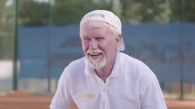 Stående av ett moget säkert koncentrerat mananseende på en tennisbana som är klar att spela Rekreation och fritid arkivfilmer