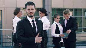 Stående av ett nöjt överlägset och hans kollegor i bakgrunden lager videofilmer