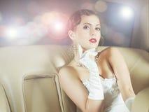 Stående av ett rikt kvinnasammanträde i en bil arkivfoto