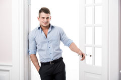Stående av ett smart allvarligt sexigt anseende för ung man i dörröppningshemmiljön Arkivbild