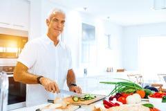 Stående av ett smart anseende för hög man i kök arkivfoto