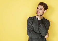 Stående av ett smart anseende för ung man mot gul backgroun arkivbilder