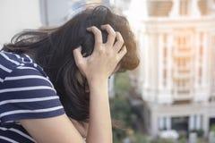 Stående av ett stressat asiatiskt kvinnainnehavhuvud i händer med stadsbyggnadsbakgrund royaltyfri bild
