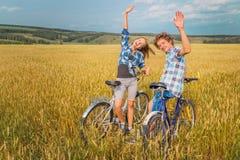 Stående av ett tonårigt på en cykel mot den blåa molniga himlen och yelen arkivbilder