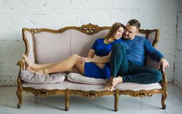 Stående av ett trendigt stilfullt par som sitter samman med kal fot på soffan i vardagsrummet, omfamna som ler, royaltyfri foto