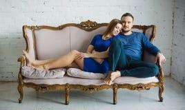 Stående av ett trendigt stilfullt par som sitter samman med kal fot på soffan i vardagsrummet, omfamna som ler, fotografering för bildbyråer