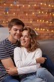 Stående av ett ungt älska par som tillsammans vilar på en hemmastadd grå soffa och att krama arkivbilder