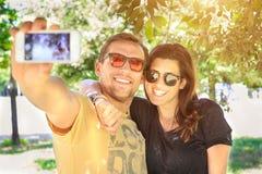 Stående av ett ungt attraktivt turist- par genom att använda en smartphone för att ta en selfiebild och att ha emotionell gyckel  Arkivbild