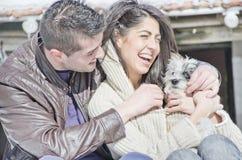 Stående av ett ungt förälskelsepar och deras hund Arkivfoto