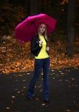 Stående av ett ungt härligt flickaslut upp under det rosa paraplyet i regnigt höstväder i parkera Arkivbild