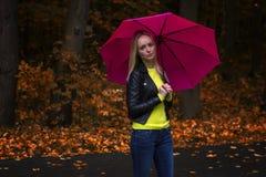 Stående av ett ungt härligt flickaslut upp under det rosa paraplyet i regnigt höstväder i parkera Royaltyfria Bilder
