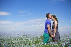 Stående av ett ungt härligt gravid par i linnefält Royaltyfri Bild